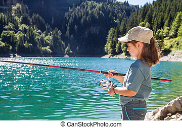 young girl fishing in a lake in the