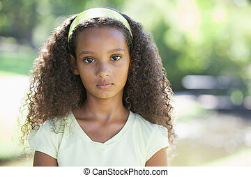 Young girl frowning at the camera in the park on a sunny day
