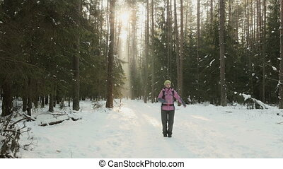 Young girl funny walks in the winter wood