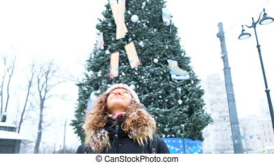 Young girl gasping snowflakes in the city with headphones on the background of the Christmas tree, closeup.