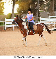 Young girl getting a horseback riding lesson