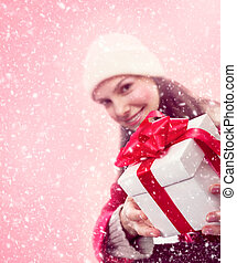 Young girl gives a christmas gift in snow