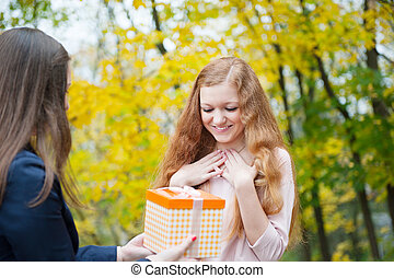 Young girl giving birthday present box