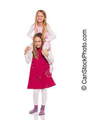 Young girl giving piggyback ride