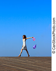 young girl goes with balloons on blue sky background