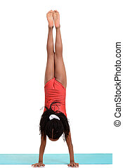 young girl doing gymnastics handstand on white background