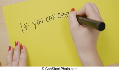 Young girl hands writing if you can dream it you can do it...