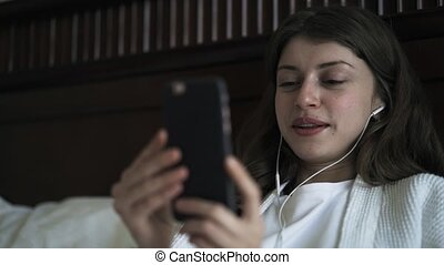 Young girl having a video call with her smartphone in bed, close up