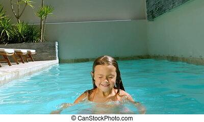 Young girl having fun in the swimmi