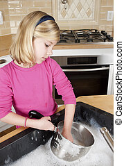 Young girl helping with cleaning by washing dishes. Girl holding cooking pot and head turned to the side.