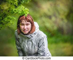 young girl hides from the rain under a bush