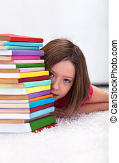Young girl hiding behind books