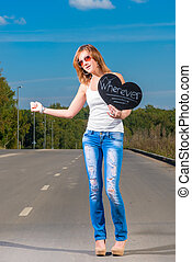 young girl hitchhiking on a country road