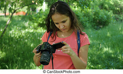 young girl holding a camera. To pose for the camera. Fun outdoors