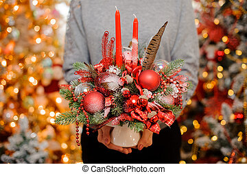 Young girl holding a christmas composition of red decor and fir-tree