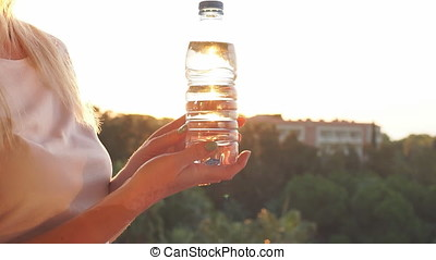 Young girl holding a drinking water bottle at sunset. Slow motion