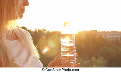 Young girl holding a drinking water bottle at sunset. Slow motion.