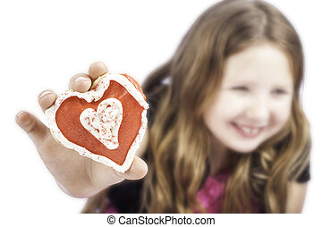 Young girl holding a heart cookie