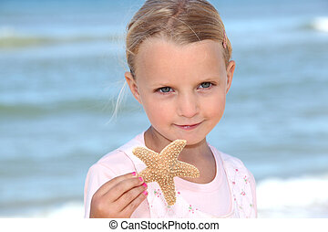 Young girl holding a starfish on the beach