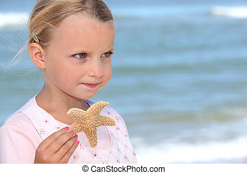 Young girl holding a starfish