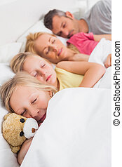 Young girl holding a teddy bear next to her sleeping family