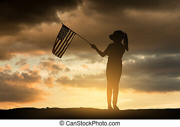 Young girl holding American flag at sunset.