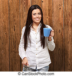 young girl holding cup against a wooden wall