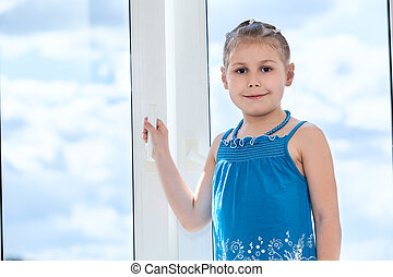 Young girl holding handle of plastic window with blue sky