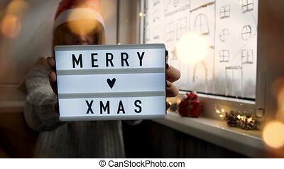 Young girl holding lightbox with text MERRY XMAS. Room with christmas decorations. Garland light. Holiday presents. Merry christmas and Happy new year.