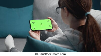 Young girl holding phone with green screen at home