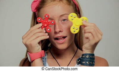 Young girl holding popular fidget spinner toy - close up portrait.