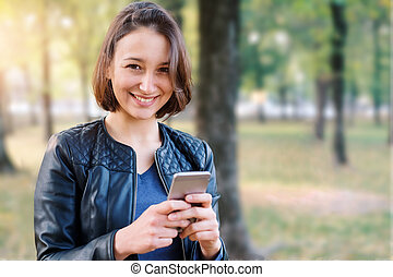 Young girl holding the mobile phone portrait and copy space for