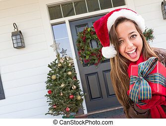 Young Girl Holding Wrapped Gift Standing on Christmas Decorated Front Porch