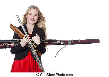 young girl holds woodwind instruments in studio - young...