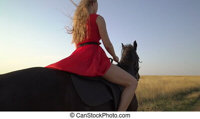 Young girl horseback rider in red dress riding black horse across grass field