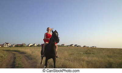 Young girl horseback rider in red dress riding black horse...