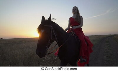 Young girl horseback rider in red dress riding horse on country road in evening