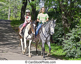Young Girl Horseback Riding - Young girl with a guide...