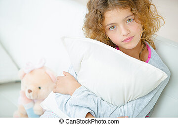 young girl hugging her pillow
