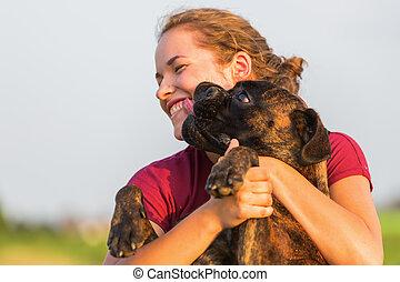 young girl hugs her boxer dog