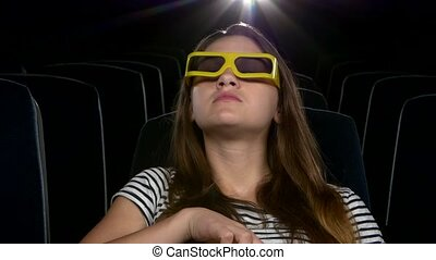 young girl in 3D at the cinema. eating popcorn. Close up