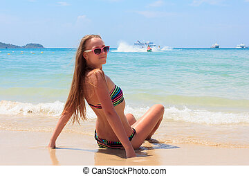 young girl in a bathing suit sitting on the beach