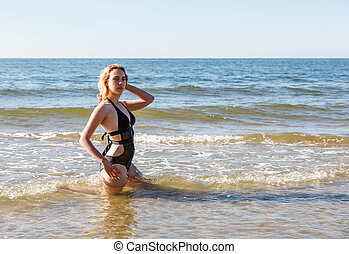 young girl in a black swimsuit sits in the water near the seashore