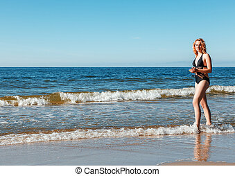 young girl in a black swimsuit stands in the water near the seashore