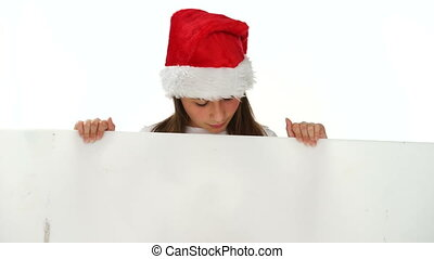 Young girl in a Christmas hat with a blank sign