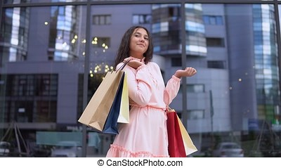 Young girl in a dress after shopping posing with packages in hands. 4K