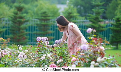 Young girl in a flower garden among beautiful roses. Smell...
