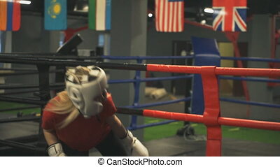 Young girl in a helmet and gloves enters the ring