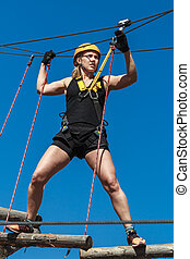young girl in a mountain helmet walks at a height on wooden logs with ropes in an alpinist adventure park against a blue sky