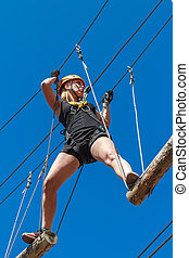 young girl in a mountain helmet walks at a height on wooden logs with ropes in an alpinist adventure park against a blue sky. training mountaineers in the mountains